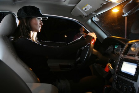 Chauffeur: Beautiful young woman driving car at night