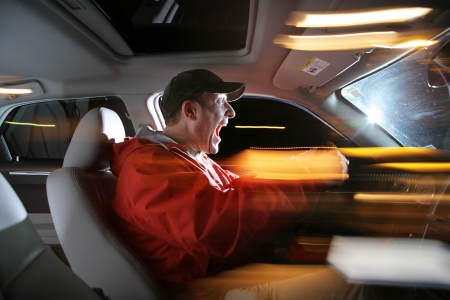 sunroof: Man driving car at night, speeding fast. Stock Photo