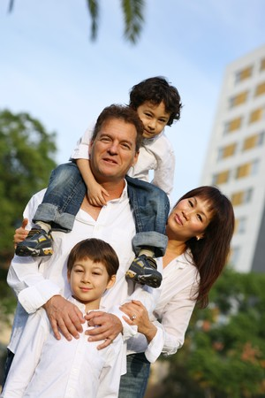 interracial family: Happy family with two sons together outdoors. Shallow DOF.