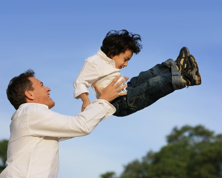 Father lifting son in the air. Shallow DOF. Stock Photo