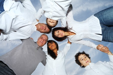 interracial family: Circle of happy people over sky.