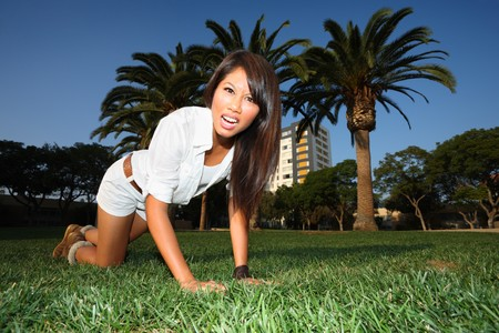 Playful young woman on green lawn. photo