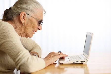 umpc: Elderly woman typing on ultra portable laptop computer. Shallow DOF.