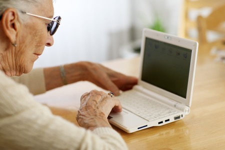 Elderly woman typing on ultra portable laptop computer. Shallow DOF. photo