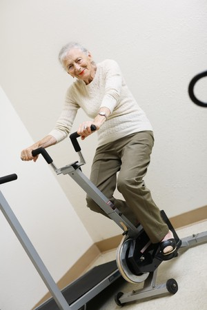 Senior woman pedaling on stationery bike photo