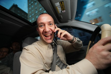 safe driving: Businessman driving in car and talking on cell phone.