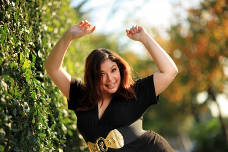 Joyful plus size woman outdoors. Shallow DOF.