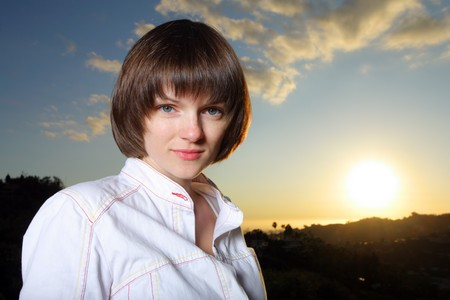 Portrait of a beautiful young woman at sunset photo