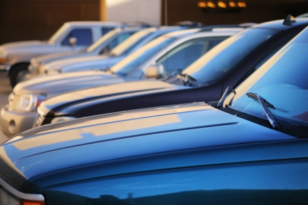 auto focus: Row of cars in parking lot. Abstract background. Shallow DOF.