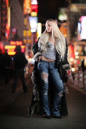 Gorgeous blond woman in fur coat standing at Times Square, New York City.