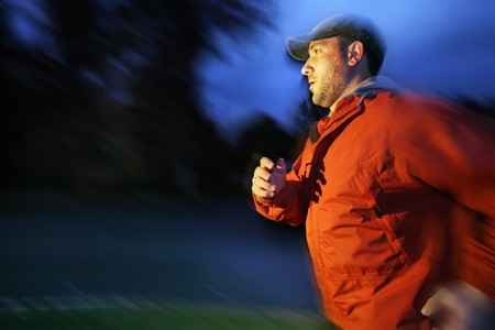 early 30s: Man running outdoors at twilight, blurred motion. Stock Photo
