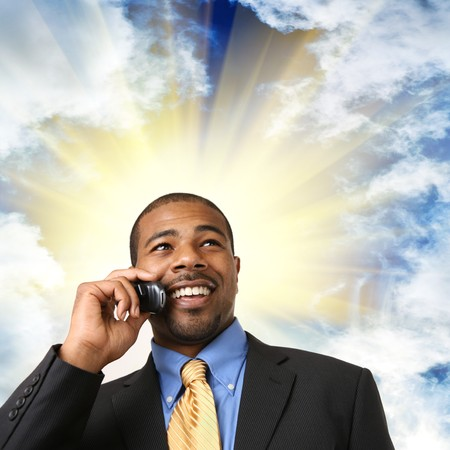 mobile: African American businessman talking on mobile phone, smiling. Close-up, isolated over white.