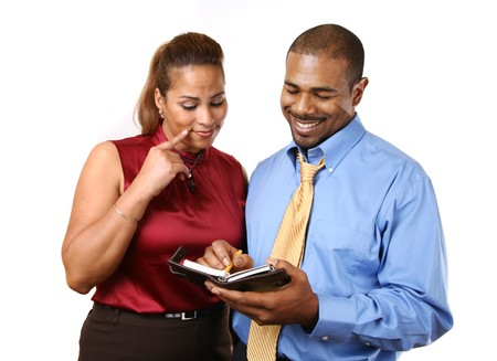 taking a wife: African American couple in business attire discussing something looking in organizer. Stock Photo