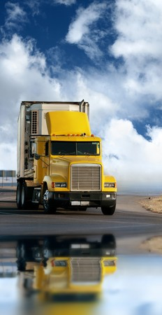 reflects: Big yellow trailer on the road over dramatic blue sky with white clouds.