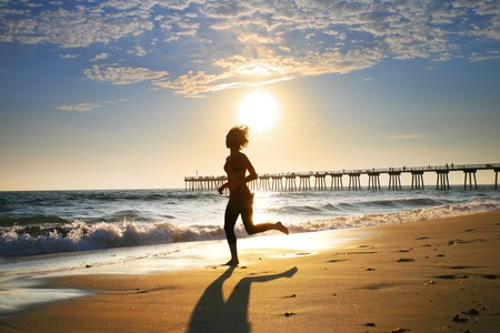 Woman at the beach running by the ocean at sunset photo
