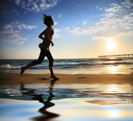 夕暮れ時、海のビーチで走っている女性