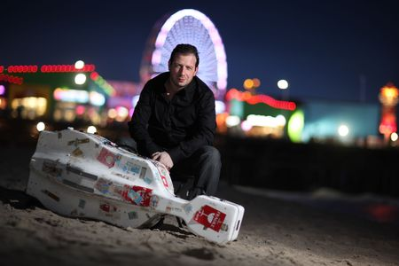 Portrait of a musician with travel cello or guitar case, sitting on beach at night. Shallow DOF. Stock Photo - 4665034