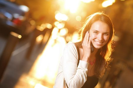 warm color: Beautiful young woman smiling and talking on cell phone on sunny street. ShallowDOF.