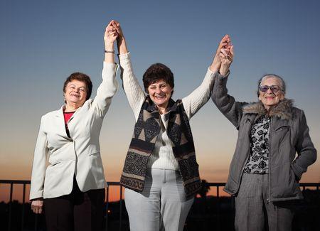 Three women raising hands photo