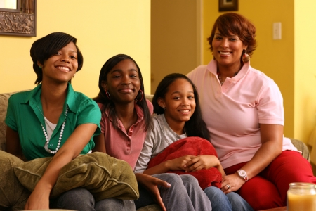 Happy mother with daughters at home. Shallow DOF, focus on the girl in front.