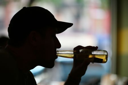 Silhouette of a man drinking bear. Close-up. photo