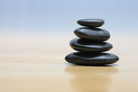 stacked stones: Zen stones on wooden surface. Shallow DOF. Stock Photo