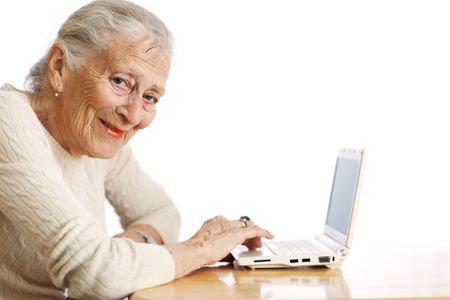 Elderly woman with ultra portable laptop computer. Shallow DOF. photo