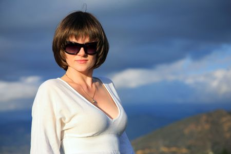 decolette: Portrait of a beautiful young woman in sunglasses with blue cloudy sky behind her. Stock Photo
