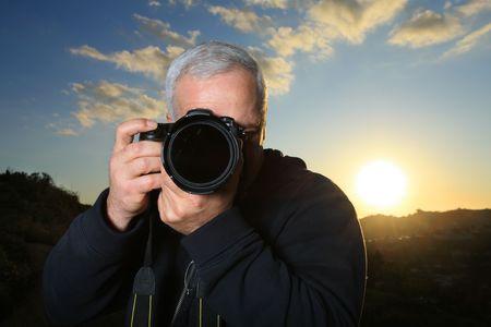 Nature photographer taking photo at sunset photo