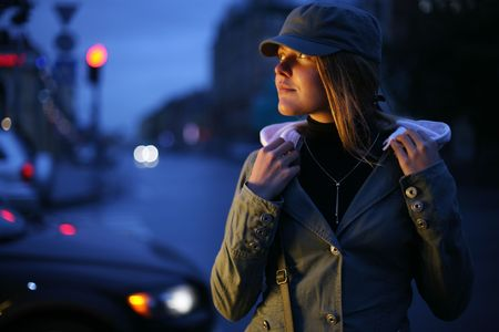 hoodie: Beautiful young woman on twilight street. Shallow DOF. Stock Photo