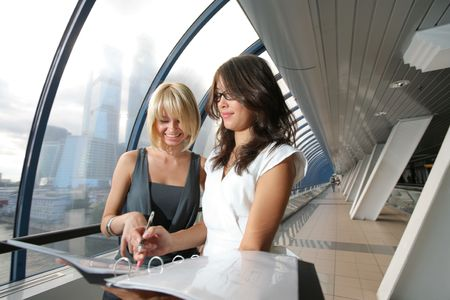 Two businesswomen looking into papers in futuristic interior Stock Photo