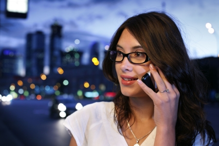 calling communication: Beautiful young woman talking on mobile phone in night city. Shallow DOF.