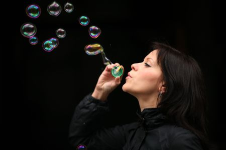 Portrait of a beautiful young woman blowing bubbles photo