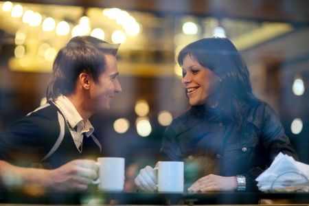drinking coffee: Feliz pareja de j�venes en el caf�, con un gran tiempo juntos. Ver caf� a trav�s de la ventana.