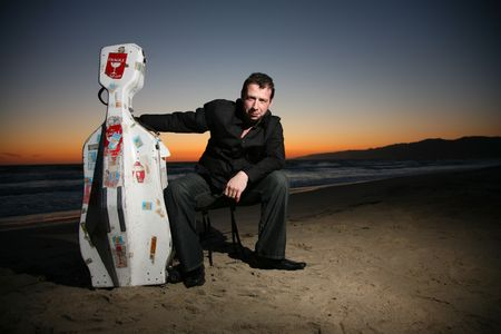 Portrait of a musician with travel cello or guitar case, sitting on beach at night. Shallow DOF. photo