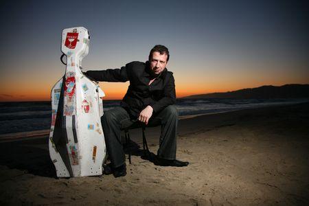 guitar case: Retrato de un m�sico con cello de viaje o estuche de guitarra, sentado en la playa por la noche. Shallow DOF.