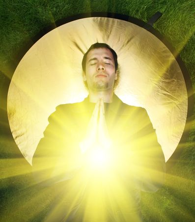 Young man meditating with rays of light coming out of his body. 스톡 콘텐츠