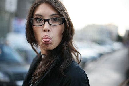Young asian businesswoman sticking out her tongue. Shallow DOF.