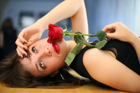 Lonely young woman with red rose, crying. Close-up, shallow DOF. photo