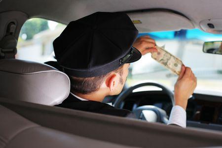 Taxi driver checking dollar bill