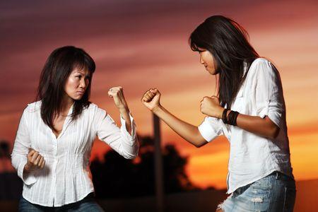 Op Aziatische vrouwen die een strijd buitenshuis bij zonsondergang