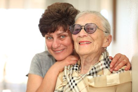 care at home: Happy woman with elderly mother, laughing together. Shallow DOF, focus on the senior woman.