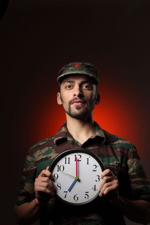 Portrait of a soldier holding clock set at 7AM