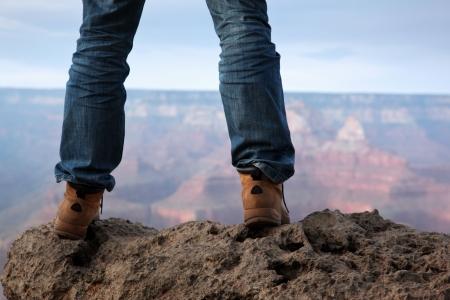 L'homme dans les bottes de randonnée debout sur le bord d'une falaise à Grand Canyon, en Arizona.