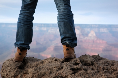 edges: Man in hiking boots standing on edge of a cliff in Grand Canyon, Arizona.