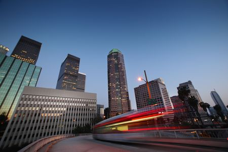 Bus speeding in downtown Los Angeles at twilight.
