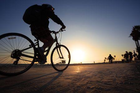 Biker silhouette riding along beach at sunset Stock Photo