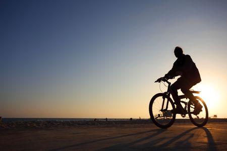 Biker silhouette riding along beach at sunset photo