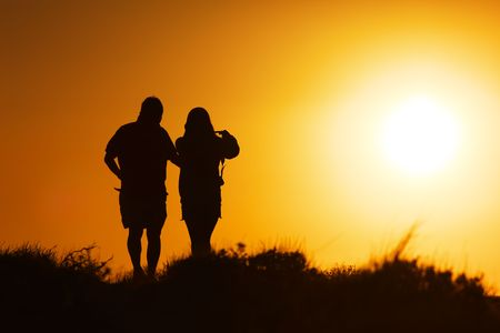 Silhouette of a couple walking at sunset