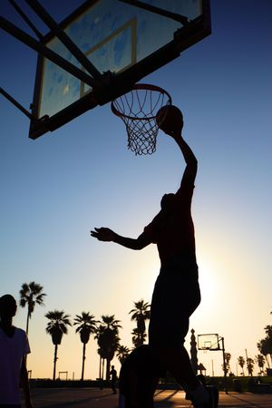 Basketball player silhouette at sunset photo
